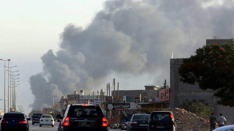 De la fumée visible à proximité de l'aéroport international de Tripoli (Libye), où des milices rivales s'affrontent, le 24 juillet 2014. (MAHMUD TURKIA / AFP)