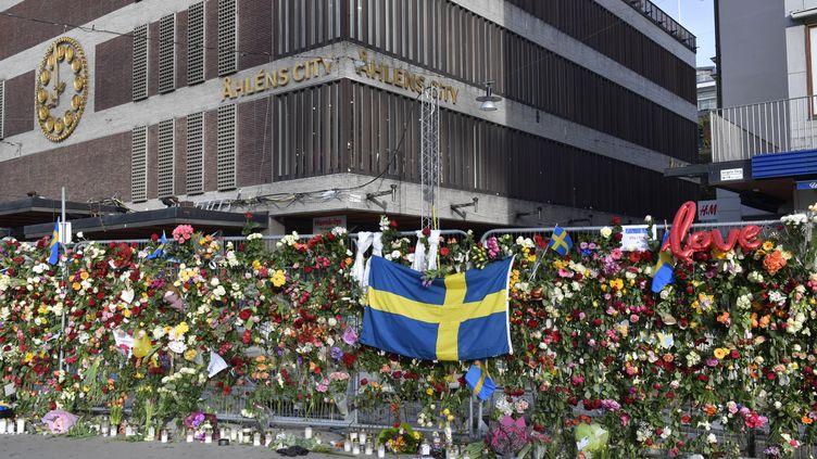 Des fleurs et des bougies ont été placées sur une barrière à Stockholm (Suède), en hommage aux victimes, le 9 avril 2017. (JONAS EKSTROMER / TT NEWS AGENCY / AFP)
