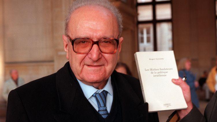 """L'intellectuel Roger Garaudy pose au côté de son livre """"Les Mythes fondateurs de la politique israélienne"""" à l'ouverture de son procès pour négationnisme, le 9 janvier 1998 à Paris. (JL MACAULT / MAXPPP)"""