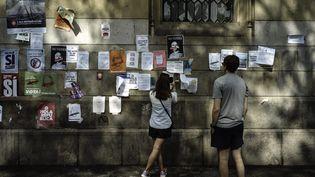 Des jeunes devant un mur avec des affiches, à Barcelone (Espagne), le 25 septembre 2017. (LOUIS WITTER / LE PICTORIUM / MAXPPP)