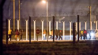 Des agents de sécurité escortent des migrants après une intrusion dans le tunnel sous la Manche, le 3 octobre 2015, près de Calais (Pas-de-Calais). (PHILIPPE HUGUEN / AFP)