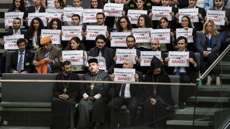 Des Arméniens tiennent des pancartes de remerciement dans le parlement allemand après le vote de reconnaissance du génocide arménien à Berlin (Allemagne), le 2 juin 2016. (ODD ANDERSEN / AFP)