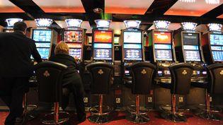 Des clients jouent aux machines à sous dans un casino en Italie, le 5 mars 2012. (ANDREAS SOLARO / AFP)