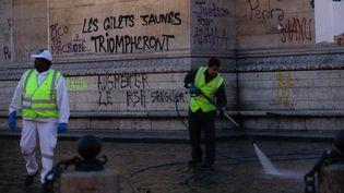 """Des ouvriers nettoient les tags autour de l'Arc de Triomphe, à Paris, au lendemain de la mobilisation des """"gilets jaunes"""", le 2 décembre 2018. (GEOFFROY VAN DER HASSELT / AFP)"""