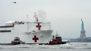 Un hôpital flottant installé sur un navire militaire américain arrive à New York, alors que l'épidémie de coronavirus flambe aux Etats-Unis. (BRYAN R. SMITH / AFP)