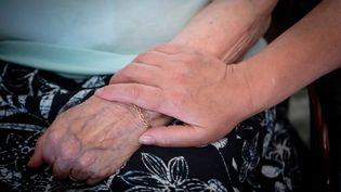 Une personne âgée est tenue par la main par une aide à domicile. (SALESSE FLORIAN / MAXPPP)