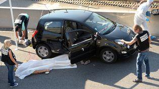 Des policiers à Marseille (Bouches-du-Rhône), sur le lieu où Adrien Anigo, le fils du directeur sportif de l'OM, a été tué, le 5 septembre 2013. (ANNE-CHRISTINE POUJOULAT / AFP)