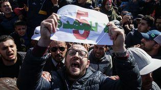 Un manifestant brandit une affiche contre le cinquième mandat duprésident Abdelaziz Bouteflika, vendredi 22 février 2019, à Alger (Algérie). (FAROUK BATICHE / DPA / AFP)