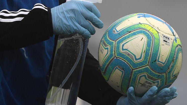 Un homme désinfecte un ballon de football avant un match, à Montevideo, en Uruguay, le 9 août 2020. (PABLO PORCIUNCULA / AFP)
