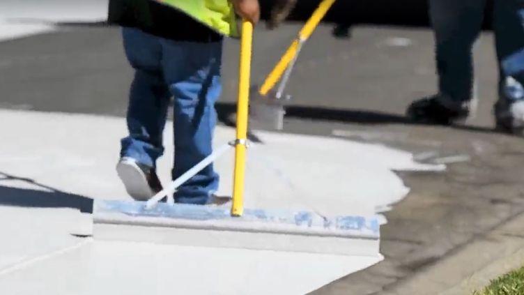 Une rue de Los Angeles (Etats-Unis) est peinte en blanc pour baisser la température urbaine, en mai 2017. (CANOGA PARK NEIGHBORHOOD COUNCIL / FACEBOOK)