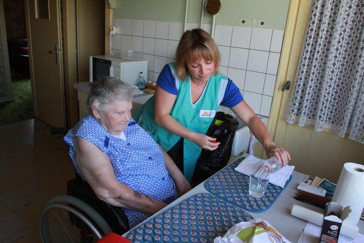 Une aide à domicile sert de l'eau à une bénéficiaire, le 29 juillet 2011, à Wittenheim (Haut-Rhin). (JEAN FRANCOIS FREY / MAXPPP)