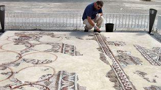 Un employé des Antiquités israéliennes travaille sur la mosaïque de 1500 ans mise au jour en 2014 àKyriat Gat (29 septembre 2015)  (Gil Cohen Magen / AFP)