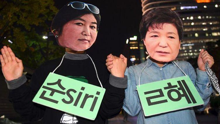 Des manifestants portent les masques des deux protagonistes lors d'une manifestation à Séoul le 27 octobre 2016. A droite la présidente de Corée du sud, Park Geun-Hye, à gauche son mentorChoi Soon-Sil. (AFP/ Jung Yeon-Je)