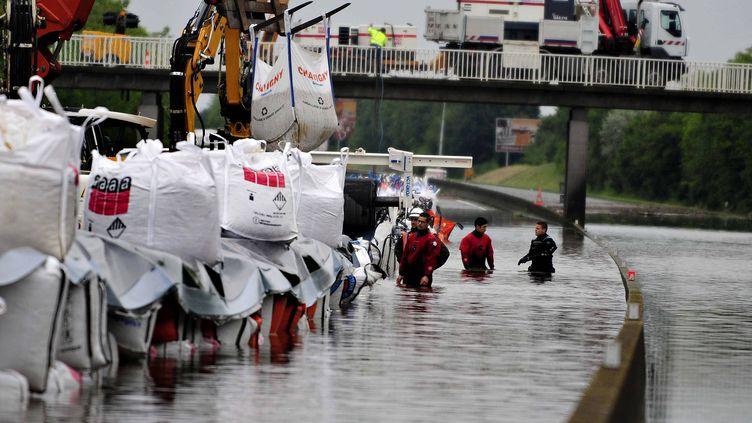 Une digue est formée avec des sacs de sable pour pomper l'eau de la chaussée de l'A10 après les inondations, en vue de récupérer les véhicules bloqués, à hauteur de Gidy (Loiret), le 4 juin 2016. (MAXPPP)