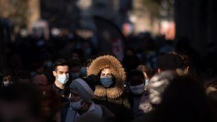 Des personnes portant un masque marchent dans la rue, le 9 janvier 2021 à Rennes. (LOIC VENANCE / AFP)
