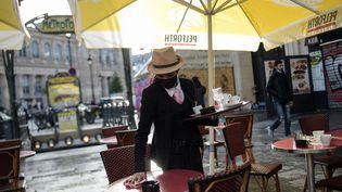 Une employée de bar nettoie une table à Paris, le 19 mai 2021, au premier jour de la phase 2 du déconfinement. (LUCAS BARIOULET / AFP)