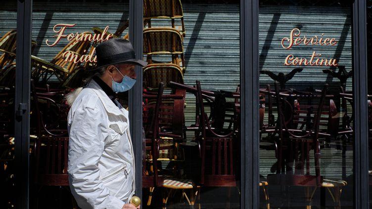 Un homme masqué passe devant un restaurant fermé, à Paris. (GREG LOOPING / HANS LUCAS)