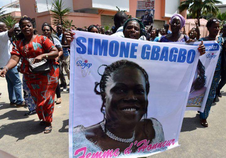 Devant la résidence de Simone Gbagbo à Abidjan, des supporters en liesse brandissent son portrait le 8 août en attendant son retour. (Photo AFP/Issoufou Sanogo)