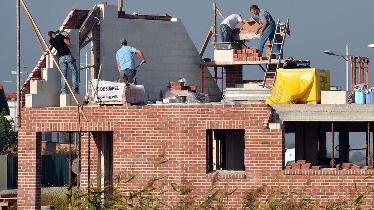 Des ouvriers travaillent le 29 septembre 2011 sur une maison en construction, à Estaires (Nord). (PHILIPPE HUGUEN / AFP)