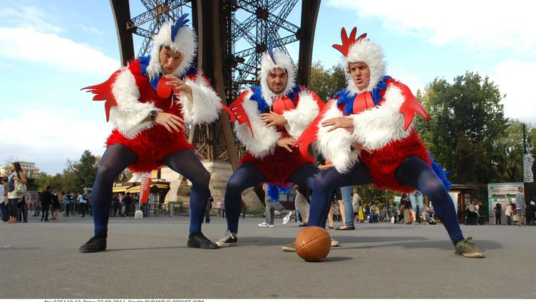 Trois supporters du XV de France posent déguisés en coqs au pied de la Tour Eiffel, le 22 septembre 2011, à Paris. (FLORENCE DURAND/SIPA)