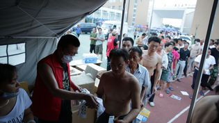 Des habitants de Tianjin (Chine), évacués de leur domicile après de puissantes explosions sur un site industriel,font la queue à l'entrée d'une tente pour obtenir des produits de première nécessité, jeudi 13 août 2015. (CAI YANG / AFP)