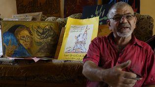 Mostafa al-Tha'i montre ses dessins le 23 mai 2017, chez lui à Hammam al-Alil.  (Simon Valmary / AFP)