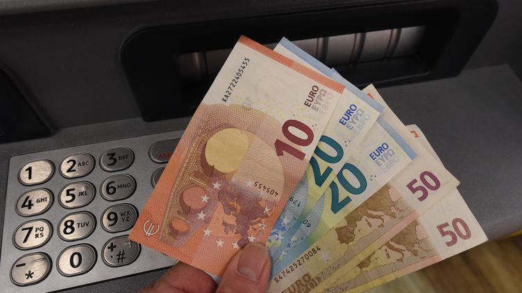 Des billets de banque à la sortie d'un distributeur automatique. (HOLGER HOLLEMANN / DPA / AFP)