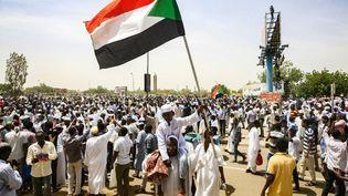 Un garçon soudanais brandit le drapeau national après que le président Omar el-Béchir a été démis. Khartoum, la capitale du Soudan, le 12 avril 2019. (AFP/EBRAHIM HAMID)
