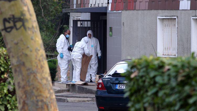 Des agents de la police scientifique et des médecins légistes pénètrent dans l'immeuble où a été tuée une femme de 47 ans, le 5 avril 2012 à Grigny (Essonne). (PIERRE VERDY / AFP)