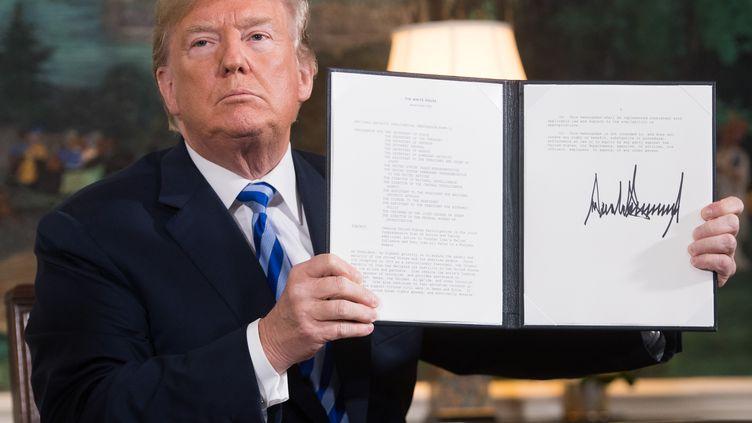 Donald Trump avec le document rétablissant les sanctions contre l'Iran après avoir annoncé le retrait américain de l'accord nucléaire iranien, le 8 mai 2018. (SAUL LOEB / AFP)