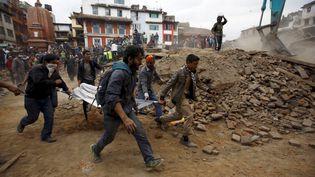 Les secours évacuent les corps et tentent de rechercher des survivants dans les décombres, après le puissant sésisme qui a touché le Népal, le 25 avril 2015, ravageant notamment Katmandou. (NAVESH CHITRAKAR / REUTERS)
