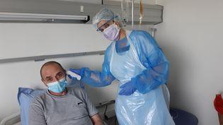 """Une infirmière prend la température de Christophe, 52 ans, atteint de """"Covid chronique"""" à l'Institut anticancer Gustave Roussy de Villejuif. (SOLENNE LE HEN / RADIO FRANCE)"""