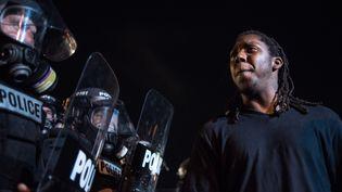 Un hommefait face à la police lors de manifestations contre les violences policières surla population afro-américaine à Charlotte (Caroline du Nord), le 21 septembre 2016 après la mort d'un homme noir par un policier. (SEAN RAYFORD / GETTY IMAGES NORTH AMERICA / AFP)