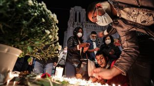 Des Niçois allument des bougies devant la basilique Notre-Dame en signe de recueillement après l'attentat, le 29 octobre 2020. (VALERY HACHE / AFP)