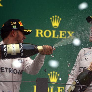 Lewis Hamilton asperge de champagne son coéquipier chez Mercedes Nico Rosberg, le 13 novembre 2016 à Sao Paulo (Brésil). (PAULO WHITAKER / REUTERS)