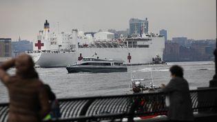 Des habitantssaluent l'arrivée d'un navire-hôpital à New York (Etats-Unis), le 30 mars 2020. (SPENCER PLATT / GETTY IMAGES NORTH AMERICA)
