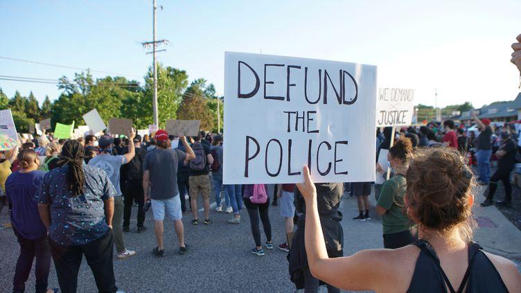 """Une manifestante brandit une pancarte """"Defund the police"""" lors d'un rassemblement contre les violences policières, le 10 juin 2020, à Florissant (Missouri, Etats-Unis). (LAWRENCE BRYANT / REUTERS)"""