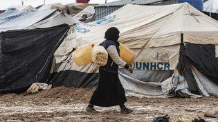 Une femme porte des jerricans, le 9 décembre 2019, dans le camp de déplacés de Al-Hol, dans le nord de la Syrie, géré par les Kurdes et où sont notamment retenus des femmes et enfants de jihadistes français. (DELIL SOULEIMAN / AFP)