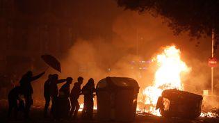 Des manifestants derrières une barricade enflammée, le 18 octobre 2019, à Barcelone. (PAU BARRENA / AFP)