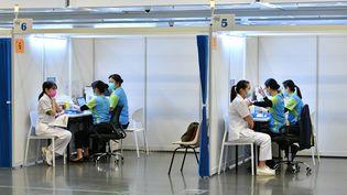 Deux femmes se font vacciner dans un centre de vaccination contre le Covid-19 à Hong Kong, le 23 février 2021. (EYEPRESS NEWS / AFP)