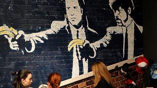 """Des visiteuses devant """"Pulp Fiction With Bananas Instead of Guns"""" de Banksy à l'exposition à l'Ifema de Madrid, le 6 décembre 2018.  (Paolo Aguilar/EFE/Newscom/MaxPPP)"""