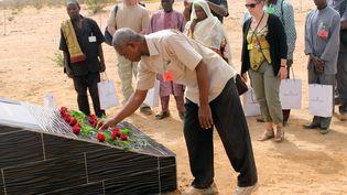 Parents et familles burkinabe et français du crash d'Air Algérie AH5017 déposent des fleurs sur une stèle près du site du crash dans la région de Gossi au Mali, à l'ouest de Gao, le 21 avril 2015. (OLLO HIEN / AFP)