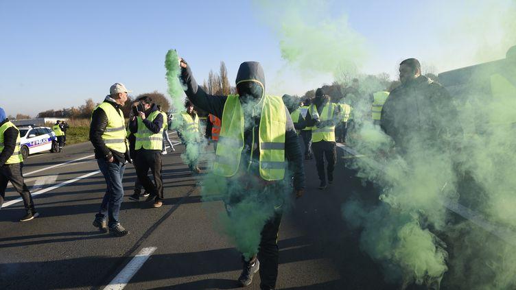 """Un manifestant branditun fumigène, le 17novembre2018, àHaulchin, près deValenciennes, dans le Nord, lors d'une manifestation des """"gilets jaunes"""". (FRANCOIS LO PRESTI / AFP)"""