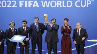 L'émir du Qatar soulève le trophée de la Coupe du monde après l'attribution de la compétition 2022 au Qatar, le 2 décembre 2010, à Zurich (Suisse). (FABRICE COFFRINI / AFP)