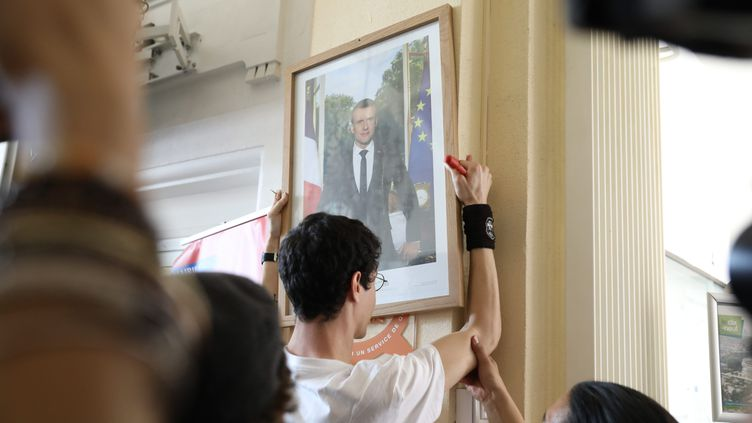 Plusieurs dizaines de défenseurs de l'environnement ont retiré le portrait officiel d'Emmanuel Macron, dans le hall de la mairie du XIXe arrondissement de Paris, le 24 mai 2019. (GUILLAUME GEORGES / MAXPPP)