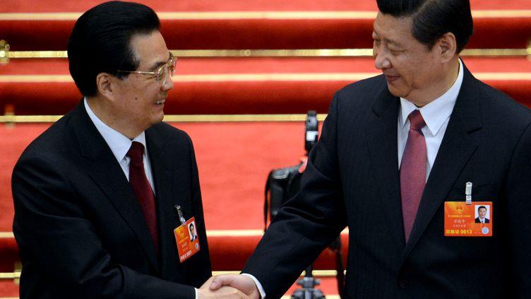 Xi Jingping, le nouveau président chinois, serre la main de son prédécesseur, Hu Jintao, à Pékin, le 14 mars 2013. (GOH CHAI HIN / AFP)