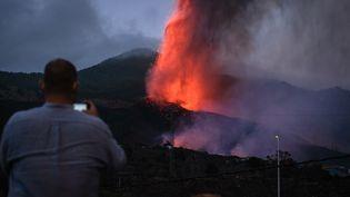 Un riverain immortalise le mont Cumbre Vieja en éruption, depuis Los Llanos de Aridane sur l'île canarienne de La Palma (Espagne), le 20 septembre 2021. (ANDRES GUTIERREZ / ANADOLU AGENCY / AFP)