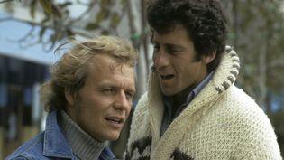 """David Soul (Hutch) et Paul Michael Glaser (Starsky) avec ce fameux cardigan qui a marqué les esprits au début de la série, lors d'une séance de photos promotionnelles de la série """"Starsky et Hutch"""" datée du 16 juin 1975 (ABC Photo Archives / Getty Images)"""
