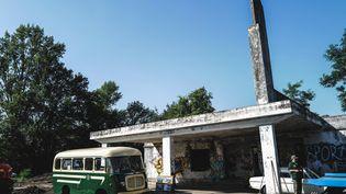 Des membres d'une association d'automobilistes participent aux travaux de restauration d'une ancienne station-service abandonnée des années 1950 le long de l'ancienne route nationale 7 au Coteau, près de Roanne, dans le centre de la France, le 13 août 2021. (OLIVIER CHASSIGNOLE / AFP)