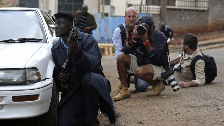 Un policier kényan et des photographes aux abords du centre commercial Westgate, à Nairobi (Kenya), visé par une attaque terroriste des shebabs somaliens, le 23 septembre 2013. ( REUTERS)